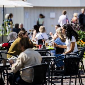 Människor äter och dricker på terrassen på Senatstorget i Helsingfors i juli 2020.
