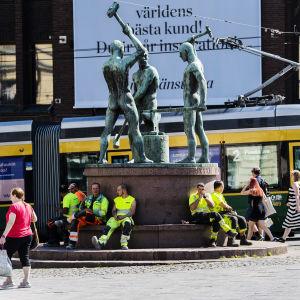 Kuvassa rakennusmiehet istuvat Kolmen sepän patsaalla heinäkuussa 2020.