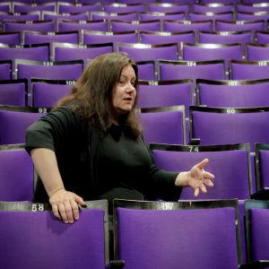 Toimittaja, teatteriohjaaja Susanna Kuparinen tyhjässä teatterikatsomossa.