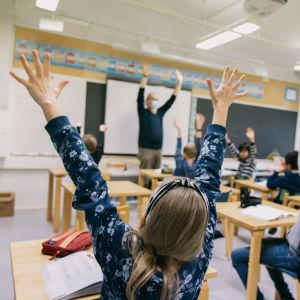 Oppilaat kädet ilmassa koululuokassa.
