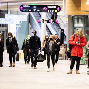 Människor i munskydd inne i en bussterminal i Helsingfors.