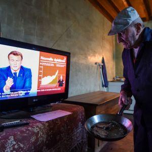 Äldre man med en stekpanna i handen står framför en tv där en kostymklädd man talar.