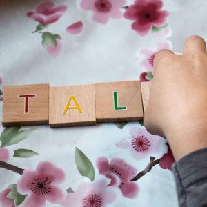 Kuvassa on lapsen käsi, joka laittaa puukirjaimia järjestykseen. Kirjaimista muodostuu sana talo.