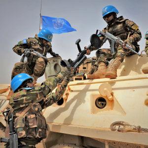 FN:s soldater på ett pansarfordon. En soldat räcker över något till en annan.