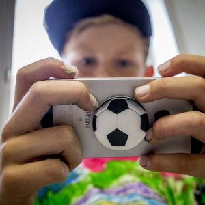 Poika pelaa kännykällä