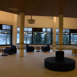 Rum med fotöljer och bord ocdh stora fönster.