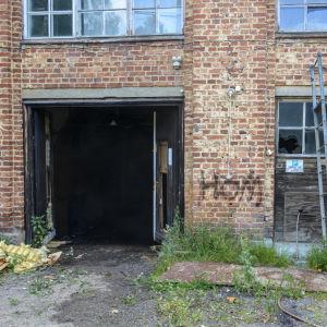 Tegelvägg med söndriga fönster och uppslagen port.