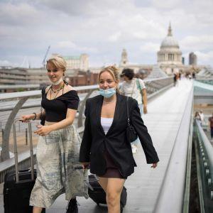 Två unga kvinnor går på Millennium Bridge i London. De bär munskydd under sina hakor.