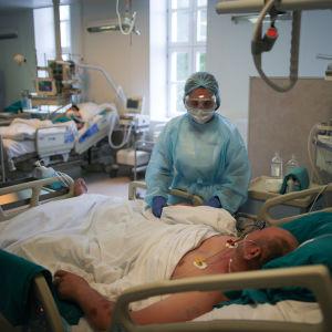 Coronavård i Ryssland. En man ligger på intensivvårdsavdelningen. En sköterska står invid hans säng.