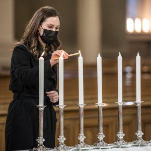 Statsminister Sanna Marin tänder ett ljus under en gudstjänt i Helsingfors domkyrka.