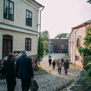 A group of people walking in Suomenlinna between buildings.