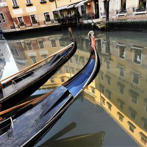 Gondolit odottavat tyhjinä hiljaisessa Venetsiassa kanavan laidalla.