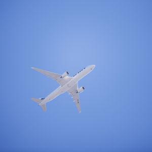 Ett vitt flygplan fotograferat nerifrån mot en bakgrund av blå himmel. Det är ett Finnairplan som flyger över Böle i Helsingfors i juni 2020.