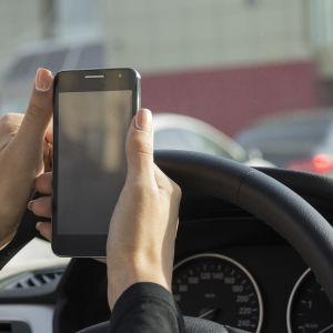 En bilförare håller en smarttelefon.