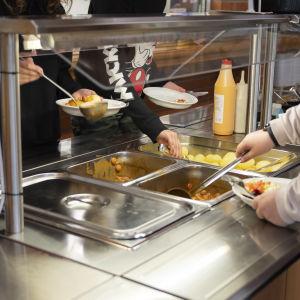 Oppilaat ottavat nakkikastiketta ruokalinjastolla.