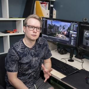 Teemu Jyrkinen istuu tietokoneen näyttöjen ääressä. Näytöillä tietokonepeli.