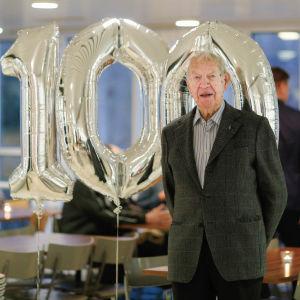 Hundraåringen Jaakko Estola poserar framför silverballonger med siffrorna 100.