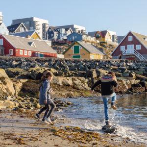 Två barn leker på en strand i Nuuk, Grönland.