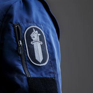 en polismärke på en blå polisjacka