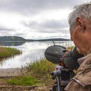 En man tittar in i en kikare mot havet.