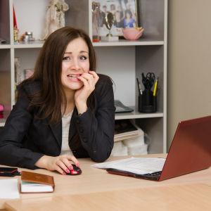 Kvinna i kavaj sitter framför laptop och biter generat på sina naglar