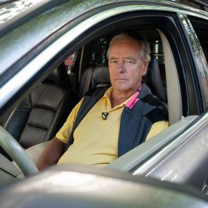 Man sitter bakom ratten i sin personbil och ser mot kameran.