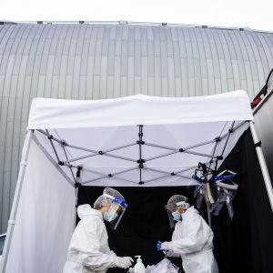 Två personer som jobbar med coronatestning står vid en drive in-teststation.
