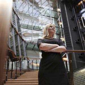 Riikka Purra med armarna i kors, fotograferad nerifrån i nya riksdagshusets trappor.