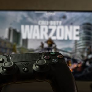 En playstationkontroll i förgrunden, i bakgrunden syns Call of Duty på tv:n.