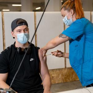 En ung man får coronavaccin.