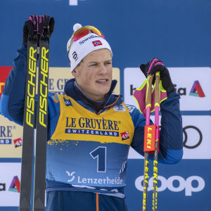 Johannes Hösflot Kläbo står med skidorna höger hand och stavarna i vänster.