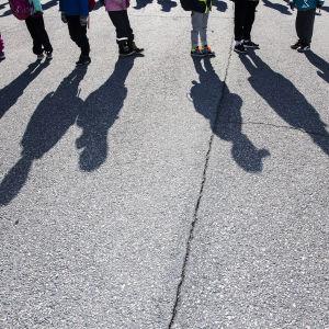 Kuvassa koululaiset kulkevat jonossa.