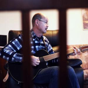 Arto Sinisalo soittaa kitaraa olohuoneessaan Lohjalla.