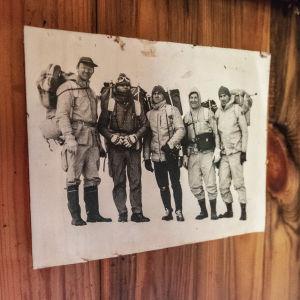 Svartvitt fotografi på trävägg. Bilden föreställer fem män med ryggsäckar och varma kläder på väg på expedition på Grönland.