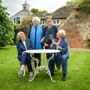 Fyra skådespelarikoner sitter i en trädgprd och skrattar.