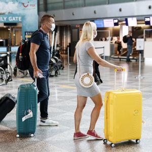 Två resenärer i ansiktsskydd går på Helsingfors-Vanda flygplats.