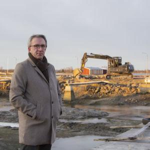 Man i grå jacka står framför den tömda hamnbassängen. I bakgrunden syns en grävmaskin.