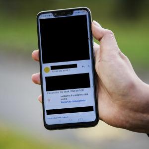 En hand som håller i en telefonskärm där man ser ett okrypterat meddelande som Vastaamo skickat. Stora delar av meddelandet har svarta rutor på sig för att gömma mottagarens personuppgifter.