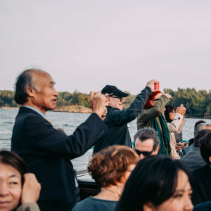A group of people taking selfies of themselves on the outside deck of a ferry boat.