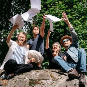 Silloin en ole yksin -kuunnelman tiimi kallion päällä heittämässä papereja ilmaan.