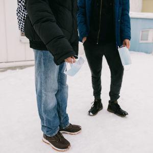 Kaksi nuorta kasvomaskit kädessään.