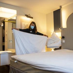 siivooja vaihtaa hotellihuoneen lakanoita