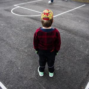 En pojke står på en asfalterad plan med ryggen mot kameran.