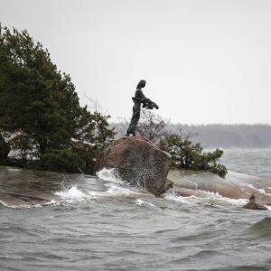 naista esittävä patsas kalliolla meren rannalla, myrsky lyö aaltoja kallioon