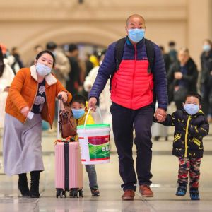 En man och en kvinna går hand i hand med två barn. De har resväskor och munskydd.