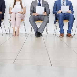 fem personer varav två är kvinnor sitter på stolar och väntar på en arbetsintervju. på bilden figurerar enbart kandidaternas ben.