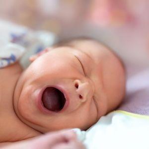 En bebis ligger på ett skötbord och gäspar.