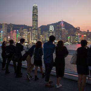 Turister tittar på solen som går ner bakom Hong Kong vid Victoria Harbour.