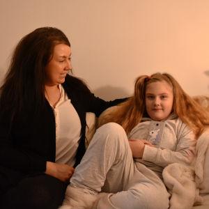 En kvinna och hennes 7-åriga dotter sitter i en soffa och ler.
