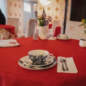 En tekopp, bestick och blomvaser på ett runt bord med röd bordduk.